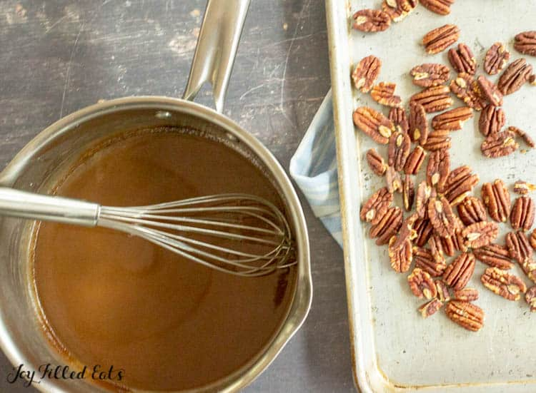saucepan of caramel sauce with whisk next to sheet pan of whole pecans