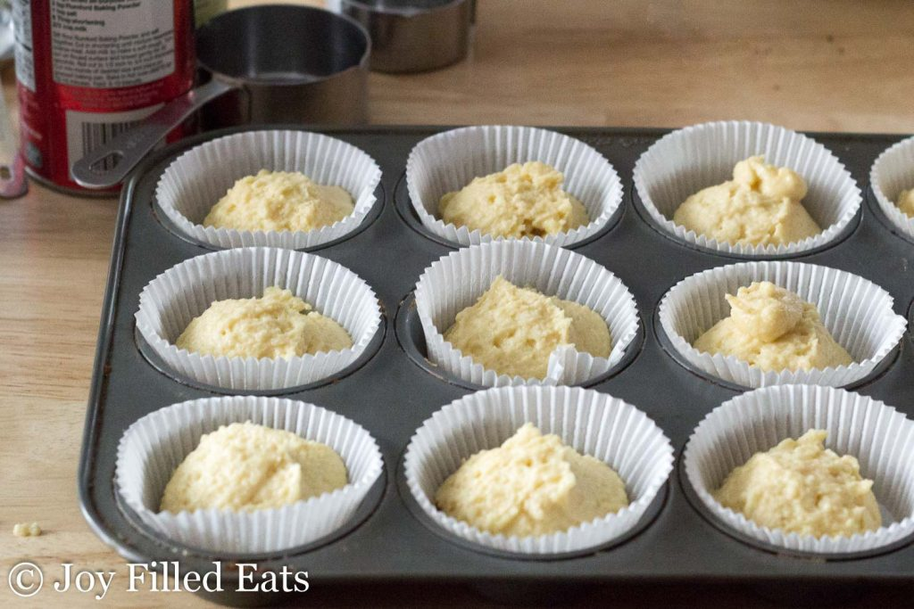 A muffin tin lined with paper liners full of batter for the keto cupcakes