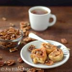 three caramel pecan sticky buns on a plate with a fork set in front of a small dish of pecans and a cup of coffee