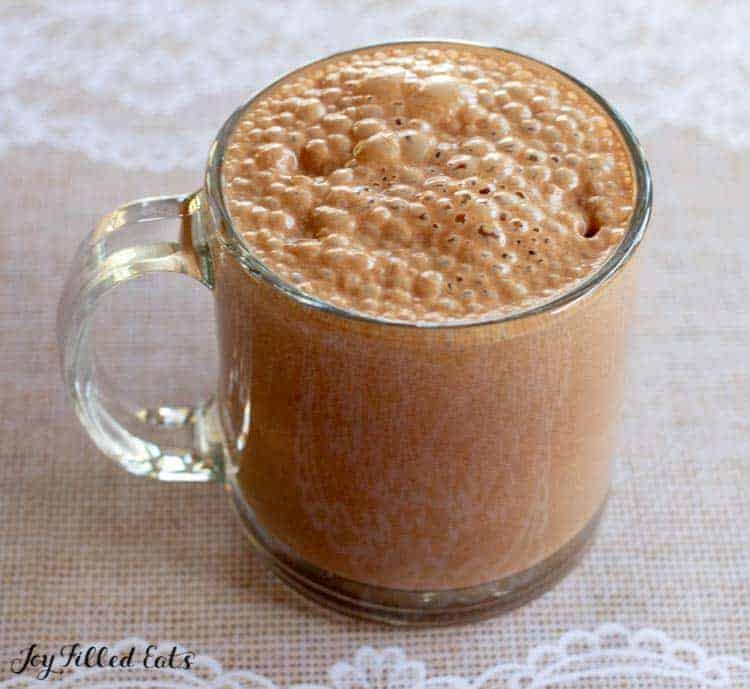glass mug filled with healthy hot chocolate close up on lace table cloth