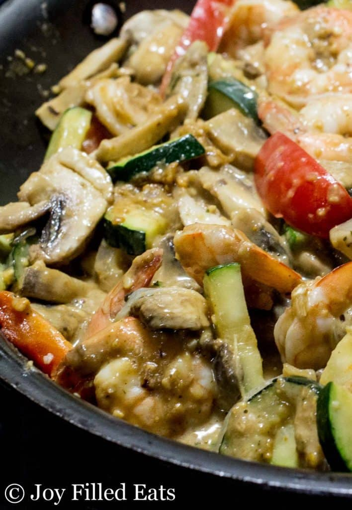 Cooked shrimp and vegetables in a frying pan with a peanut sauce