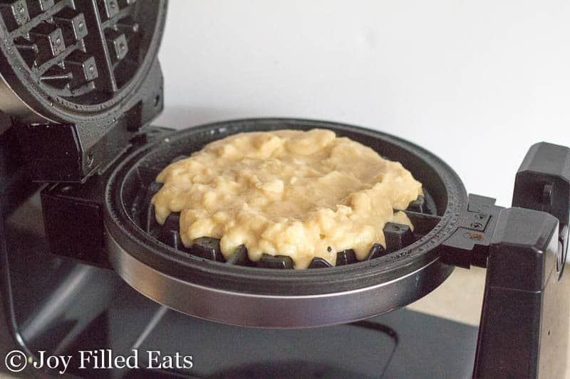 open waffle iron with coconut waffle batter poured in the center