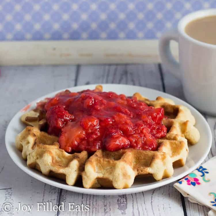 one coconut waffle topped with a fresh strawberry sauce on a white plate