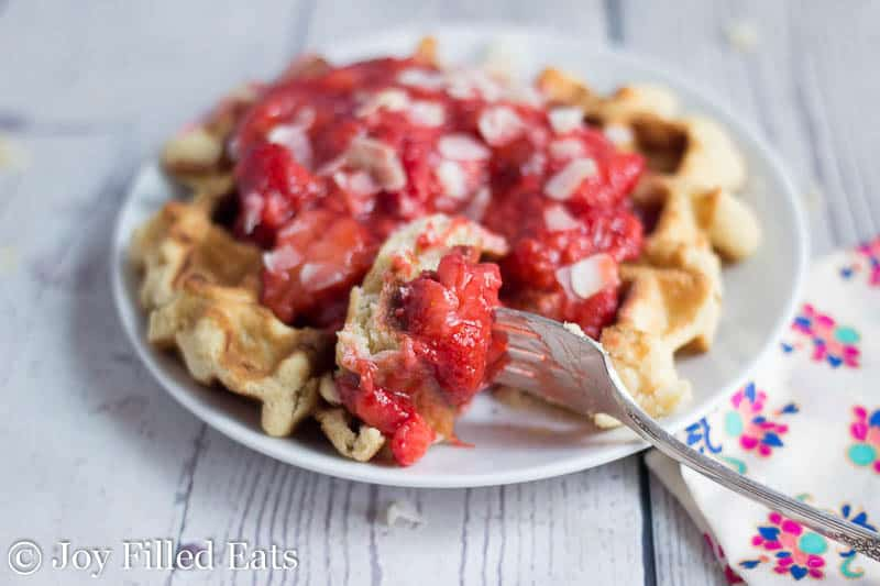 Close up of a bite of the coconut waffles with strawberries on a white plate