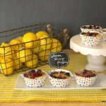 Lemon Berry Muffins on a white platter next to a baskets of lemons and cake platter with more lemon berry muffins