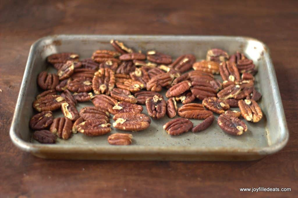 toasted pecans on a metal baking tray