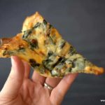 hand holding a slice of keto white spinach pizza
