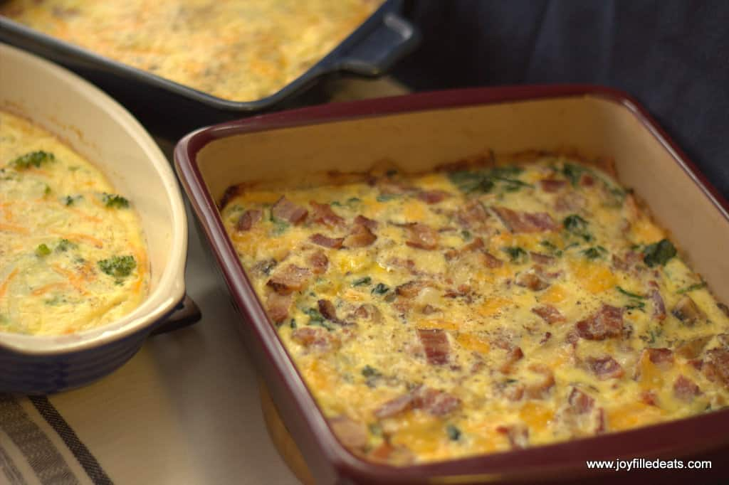 close up on square casserole dish of keto egg bake with cream cheese next to two other casserole dishes of keto egg bakes