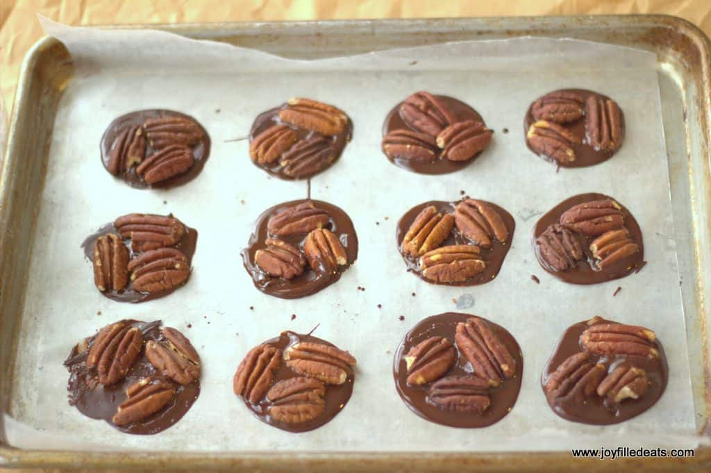 chocolate base for turtle candies topped with pecans lined on a sheet pan