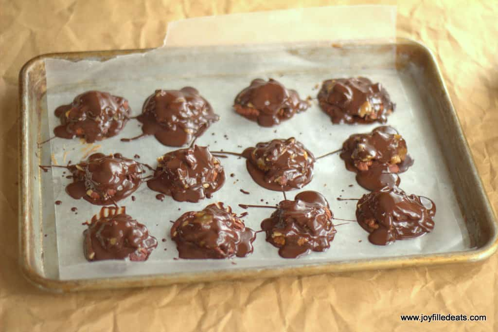 toasted coconut toffee pecan turtle candies lined on a sheet pan topped with melted chocolate
