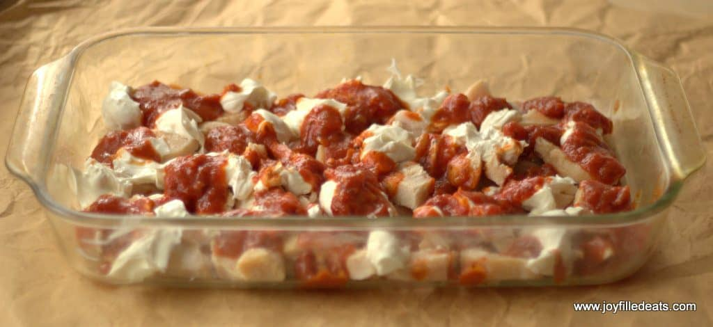 Cooked chicken topped with sauce and cream cheese in a large glass casserole dish.