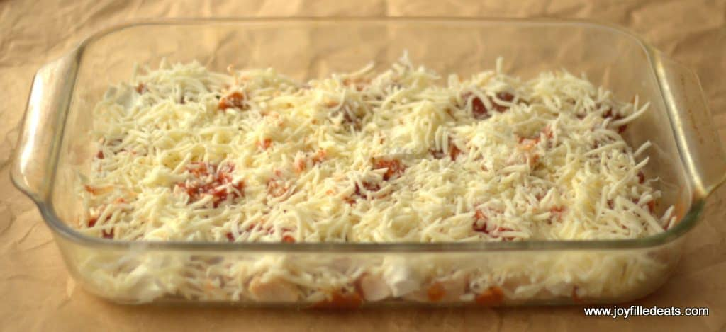 Pizza Chicken Casserole in a casserole dish with shredded cheese on top.