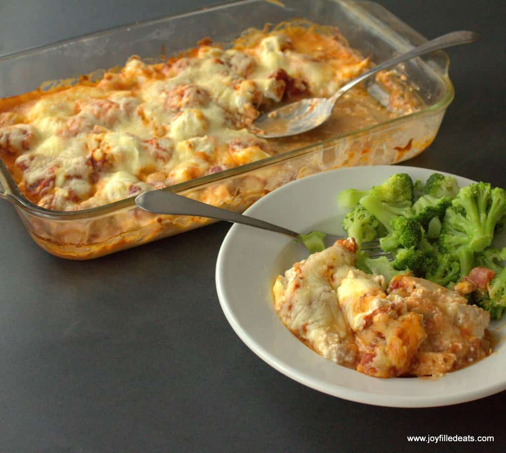 Pizza Chicken Casserole in a rectangular pyrex dish. A plate with the casserole and broccoli on the side.