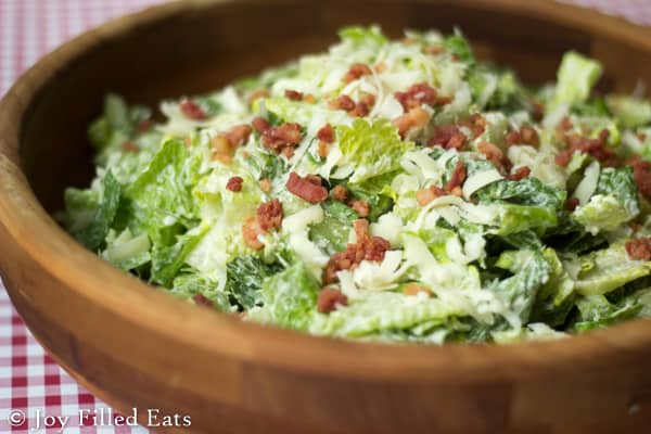 close up on Caesar salad topped with a two minute dressing and bacon bits in a wooden bowl