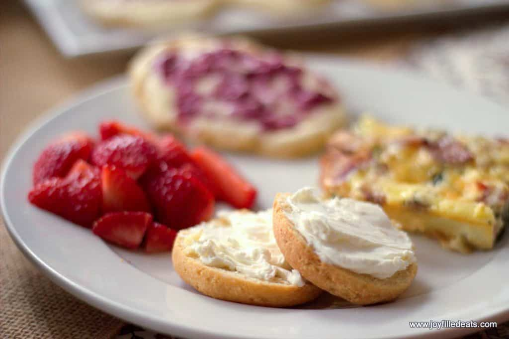 mini bagels topped with cream cheese on a plate with other breakfast foods