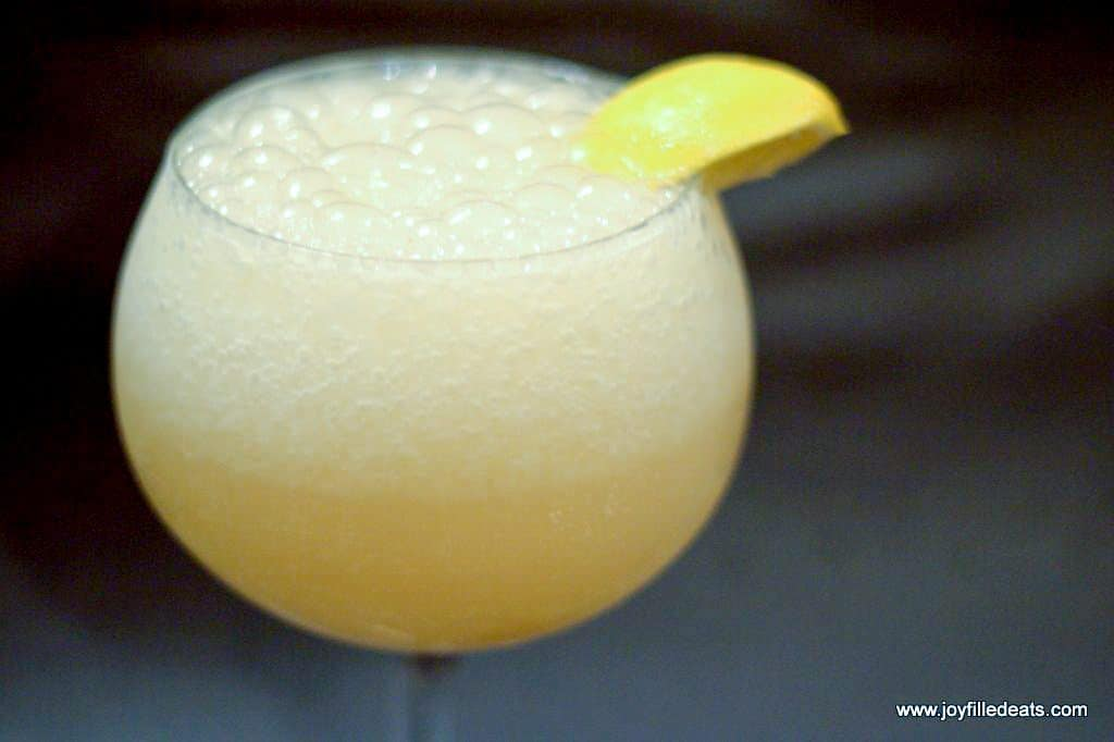 close up on glass of bubbly frozen lemonade with a lemon wedge on the rim