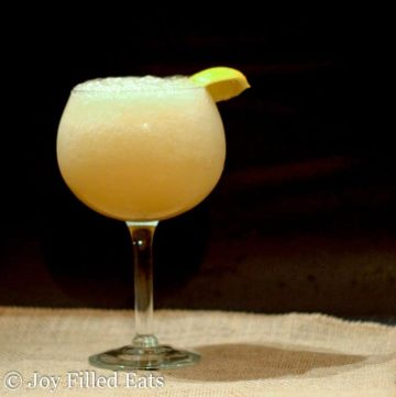 wine glass of bubbly frozen lemonade with a wedge of lemon on the rim