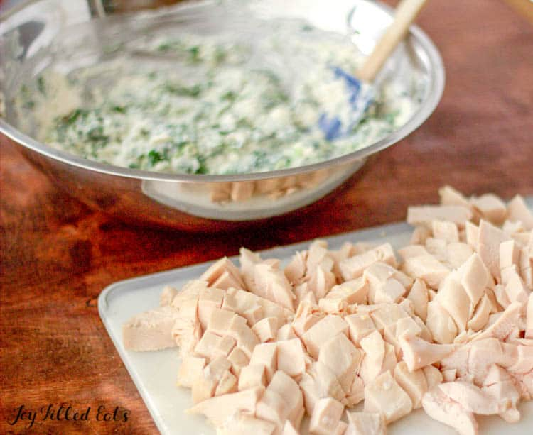 Cutting board of chicken pieces next to mixing bowl of homemade caesar seasoning