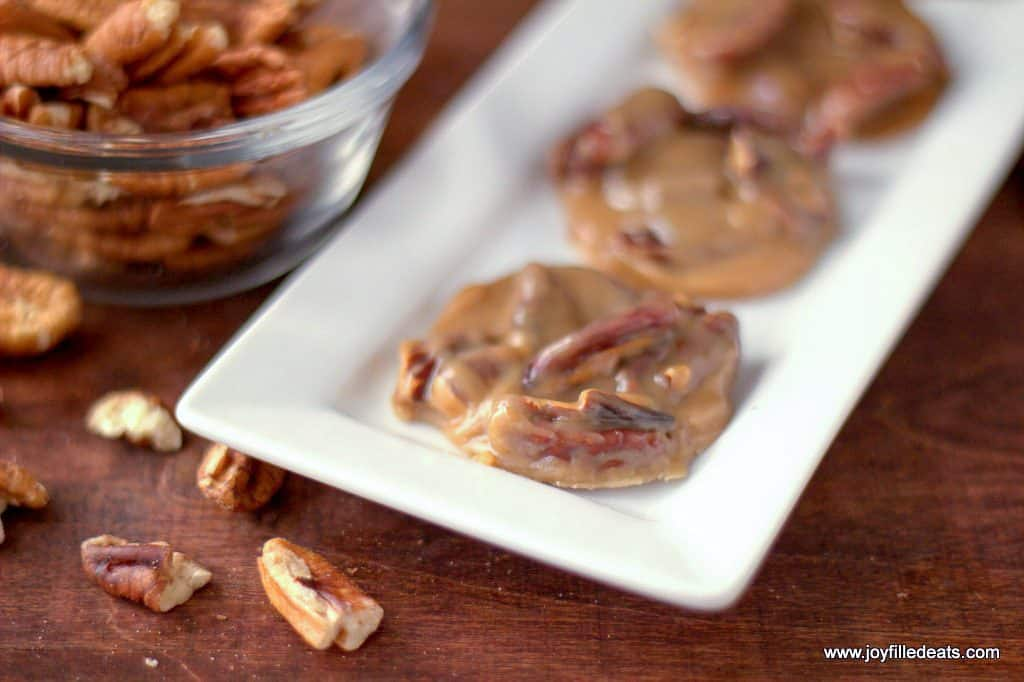 Four Pecan Pralines on a diagonal rectangular white plate sitting on a wood backdrop with pecans in a glass bowl in the corner and scattered around.