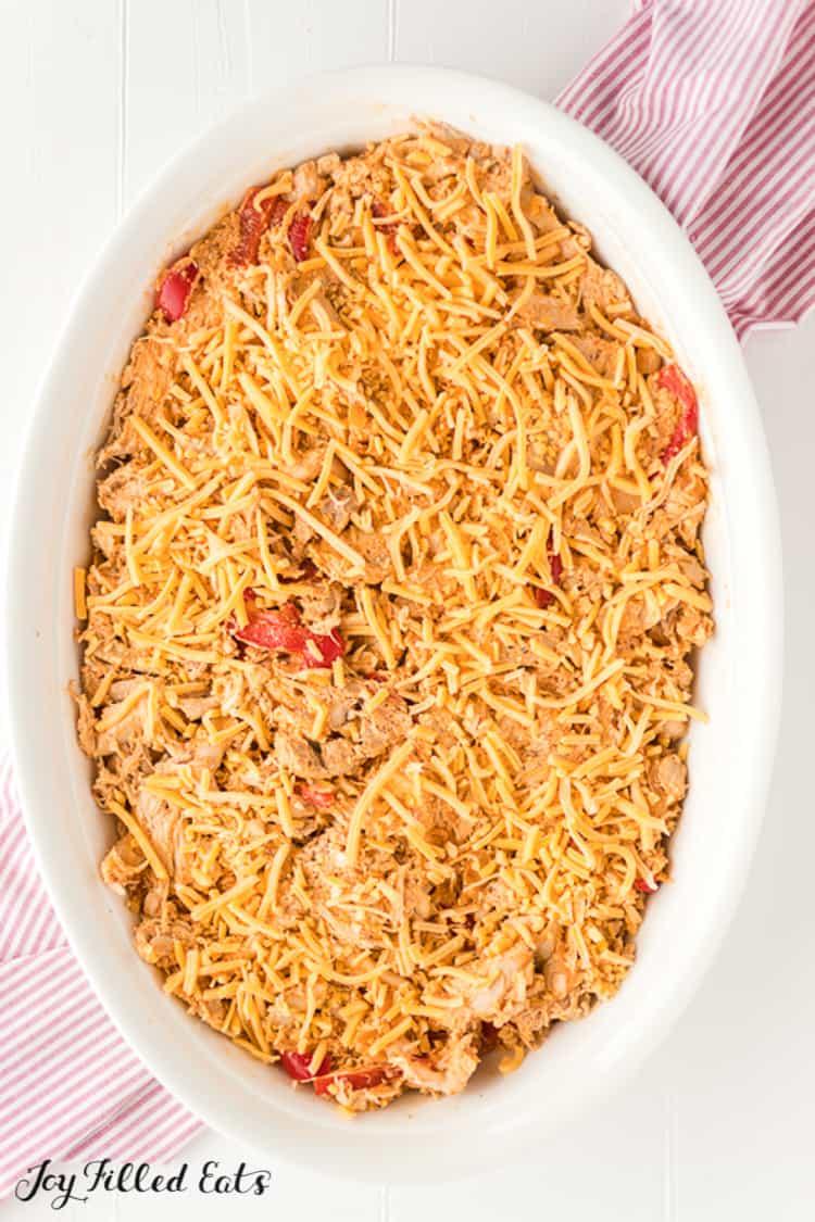 casserole dish layered with shredded cheese for chicken fajita casserole