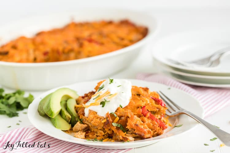 chicken fajita casserole serving on a plate topped with sour cream and served with avocado slices placed in front of casserole dish
