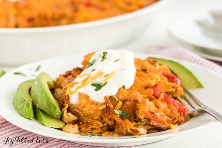 chicken fajita casserole serving on a plate topped with sour cream and served with avocado slices