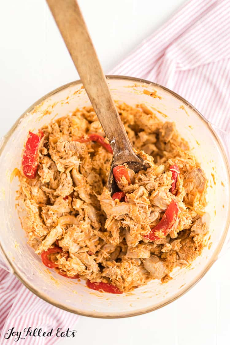 mixing bowl and wooden spoon of chicken fajita casserole filling