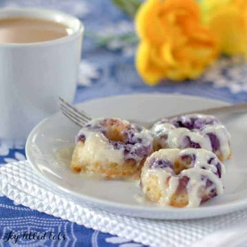 three cream cheese glazed lemon blueberry donuts on a plate with a fork set next to a cup of coffee