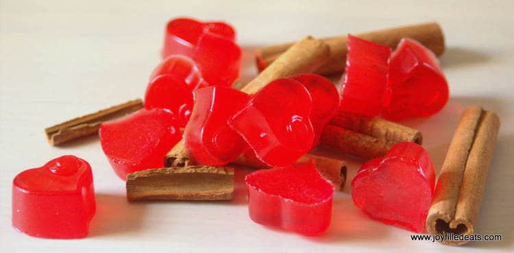 pile of sugar free red hot gummies placed on scattered cinnamon sticks