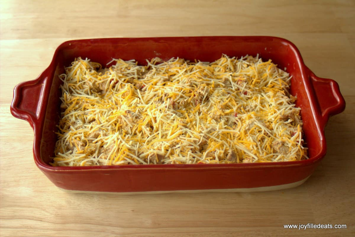 Cooked chicken onions and peppers in a red casserole dish with shredded cheese on top