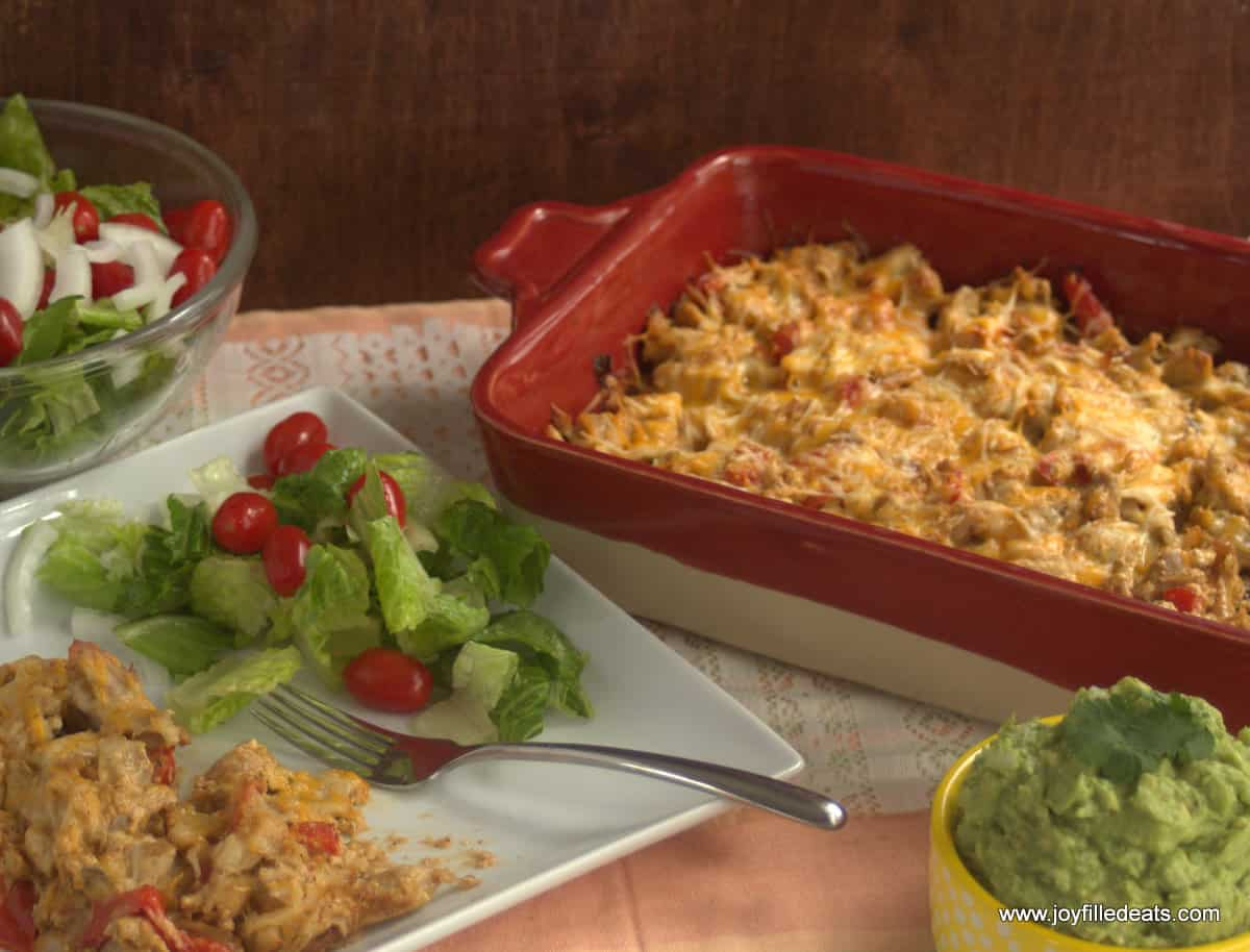 Easy Fajita Chicken Casserole baked and complete with a salad and guacamole in the background