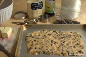 chocolate chip cookie dough formed in a large rectangle on a sheet pan