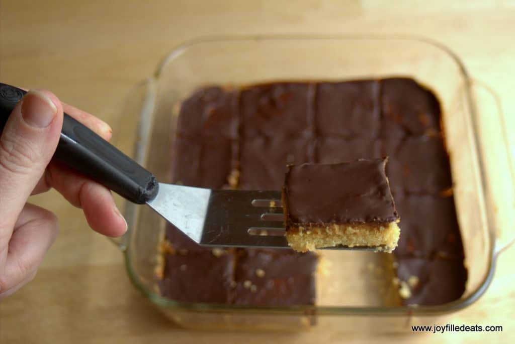 hand holding a serving spatula with a sugar free tagalong peanut butter cookie bar placed on top all above a baking dish of more cookie bars