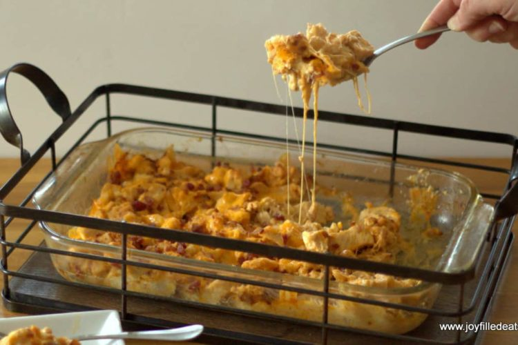 hand scooping a serving of barbecue chicken bacon casserole for glass casserole dish in a wire casserole basket