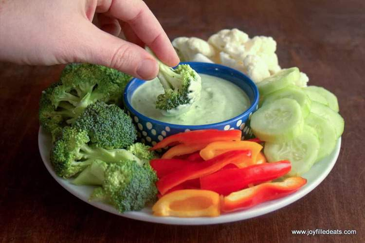 hand dipping broccoli floret into small dish of creamy chive dip surrounded by sliced vegetables