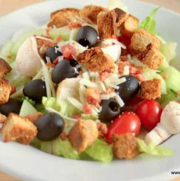 close up salad with gluten free croutons in large white bowl
