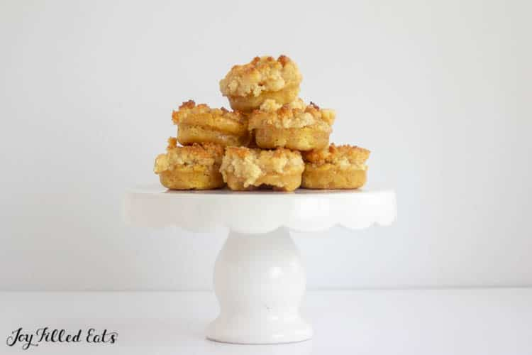 Pyramid of Keto Glazed Crumb Donuts on white cake platter