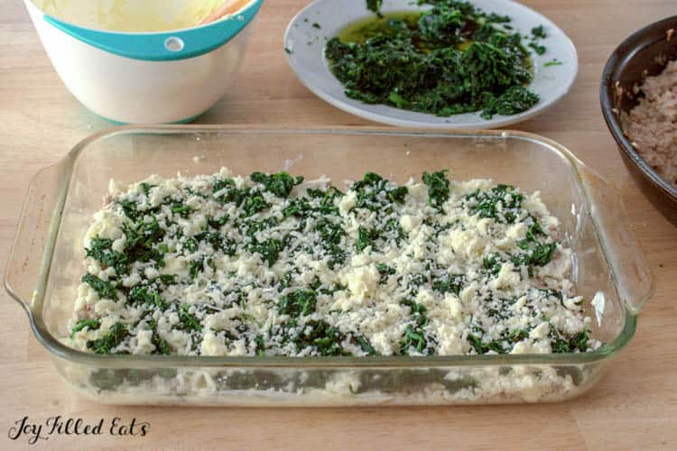 Layered casserole dish with ingredients for white keto lasagna surround by mixing bowls and plate of spinach