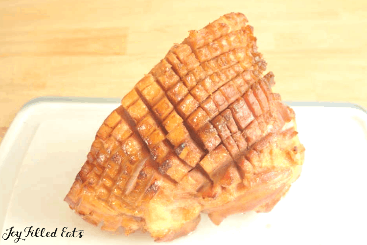 a golden cooked maple glazed ham with skin cut into a cross pattern