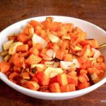 bowl full of roasted root vegetables with a utensil