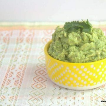 guacamole topped with a cilantro leaf in a yellow polka dot bowl placed on a decorative table cloth