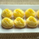 mini creamy lime curd tartlets lined on a white rectangular platter