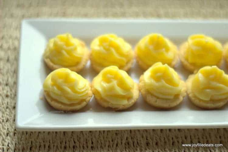 mini lime tartlets lined on a white platter