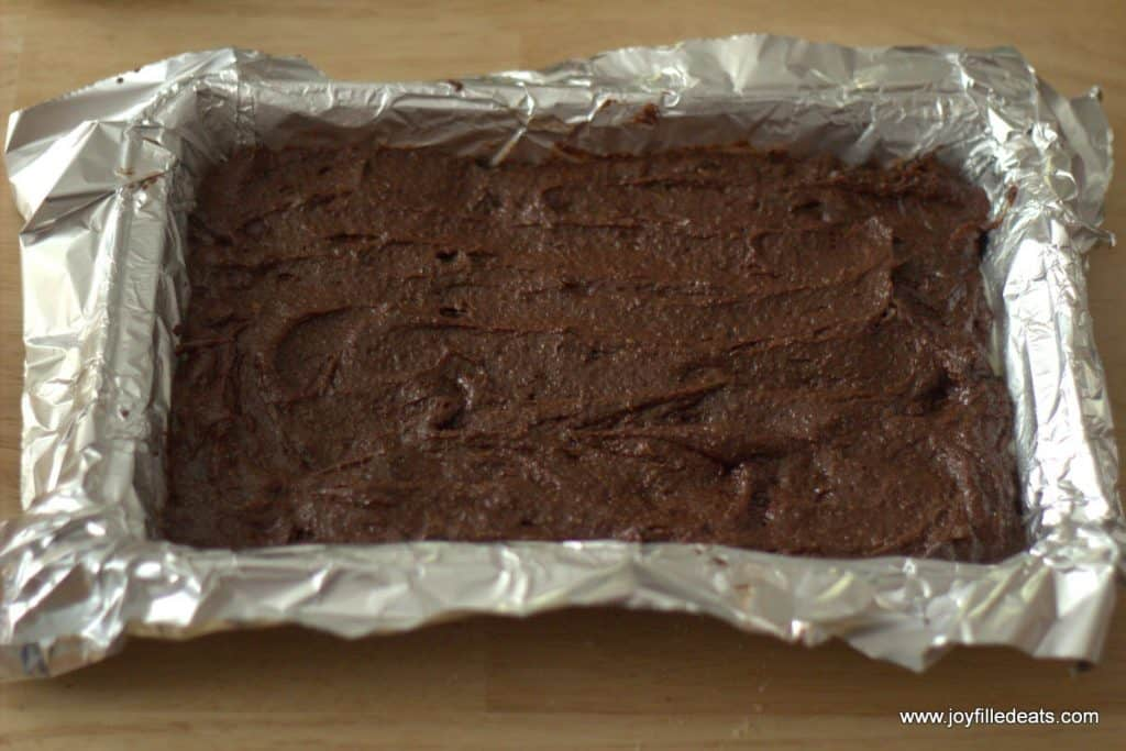 brownie batter spread into the bottom of an aluminum lined baking dish