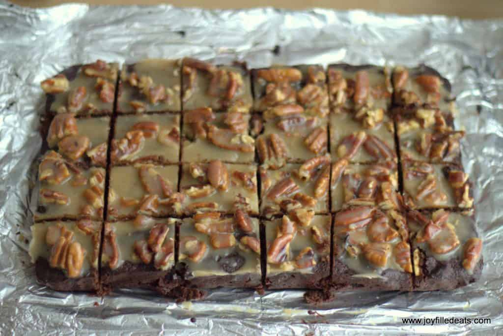 overhead view of pecan praline brownies cut into squares placed on a sheet of aluminum foil