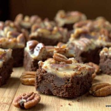 pecan praline brownies arranged on a wooden surface surrounded with scattered pecans