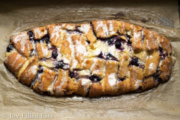 Braided Blueberry Cheese Danish with a sweet sugary glaze on parchment