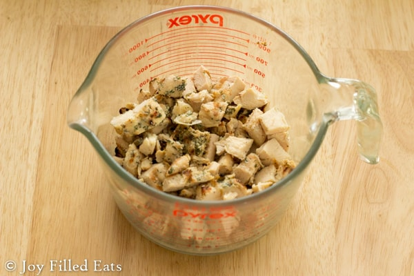 Cut up chicken for the keto chicken salad in a glass measuring cup