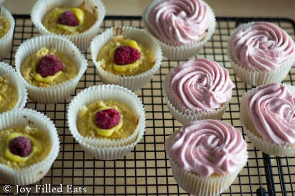 raspberry lemonade cupcakes arranged on a cooling rack, half topped with a center lemon filling with fresh raspberry and half topped with raspberry frosting