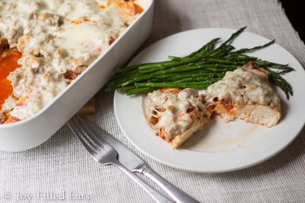 White plate and casserole dish of Italian Sausage Baked Chicken